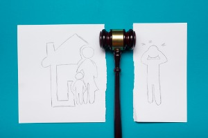 A drawn picture of divorce in Pekin IL featuring a mother and child with the father ripped separate and a gavel in between the two