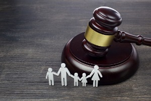 Small paper cutout of family standing in front of a gavel