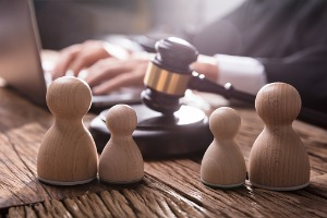 A lawyer behind a gavel and a family of wooden dolls, working on Family Law in Peoria IL